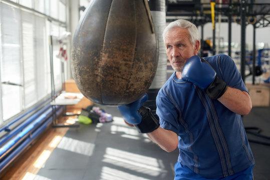 Elderly man hitting punching bag in boxing studio. Senior caucasian man in gloves beats punching bag in gym.