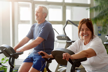 Happy senior woman working out in gym. Smiling elderly couple exercising in gym on stationary bicycle, focus on woman. Wall mural