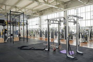 Interior of modern gym with equipment. Gymnastics ring in fitness center. Training accessories in sport club.