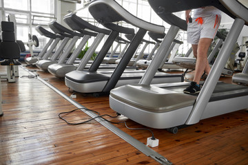 Unrecognizable man on treadmill during his training in gym. Legs of man exercising on treadmill. Gym interior with equipment. Cardio workout theme.
