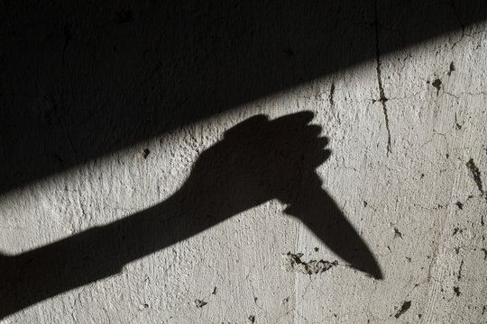 Shadow of the hand holding a knife