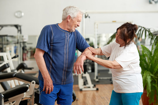 Senior man feeling pain in elbow during workout. Elderly woman holding injured arm of man at gym. Human expression of pain.