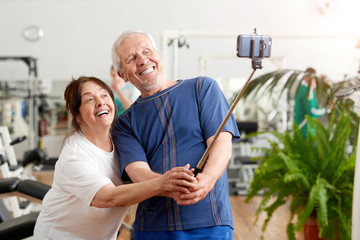 Smiling elderly couple taking selfie at gym. Beautiful senior people resting in gym taking selfie with monopod. People, sport, modern technology and leisure concept.