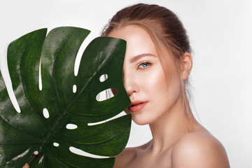 Beautiful fresh girl with perfect skin, natural make up and green leaves. Beauty face.