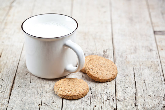 Cup of milk and some fresh baked oat cookies on rustic wooden table background.