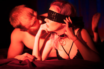 Sexy couple foreplay in bedroom at night. Concept bdsm