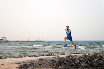 athlete runner along sea coast. running to success. summer vacation. copy space. speed concept. goal and future. people and nature. man runner focused on achievement. life as marathon or sprint