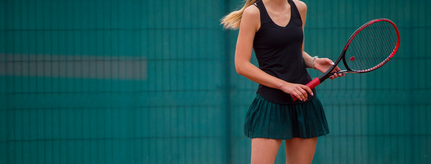 Young fit woman play tennis outdoor on orange tennis field