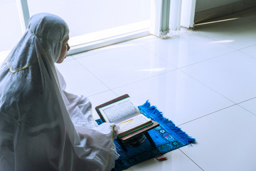 Devout woman reading Quran after doing Salat