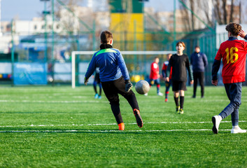 Goalkeeper hits a ball on football field. Soccer game for kids, training, football, active lifestyle for kids