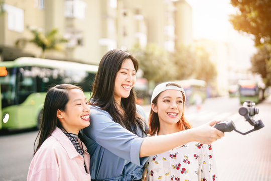 Happy Asian girls making video stories in the city center - Trendy young friends filming with gimbal smartphone  outdoor - Friendship, technology, youth people lifestyle and social media concept