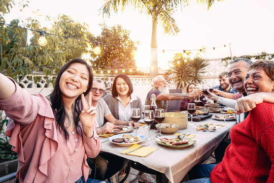 Happy family cheering and toasting with red wine glasses at dinner outdoor - People with different ages and ethnicity  having fun at bbq party - food and drink, retired and young people concept