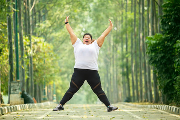 Happy obese woman jumps on the road Wall mural
