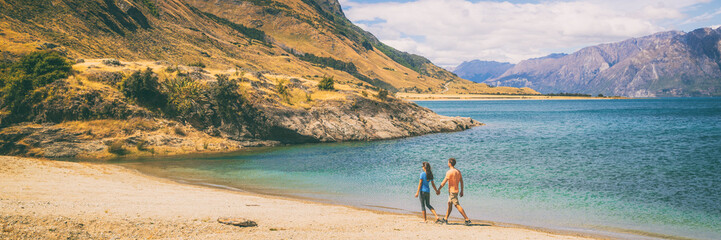 Wall Mural - New Zealand travel couple tourists walking on shore of lake Hawea in Otago region, Wanaka , nature landscape. Man and woman tramping hikers adventure lifestyle banner panorama.