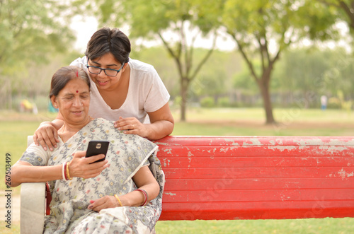 Young Indian girl with an old Indian woman looking at the mobile phone and busy talking sitting on a red bench in a park in New Delhi, India. Concept Mother's day