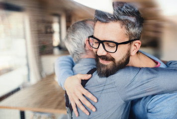 An adult hipster son and senior father indoors at home, hugging.