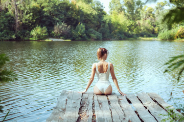 Beautiful woman in nature on the lake, she relaxes.