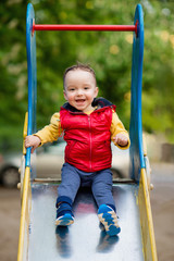 One-year-old boy plays on a playground next to a slide. He is smiling.