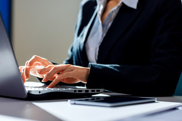 Business woman sitting at the desk and working with laptop.