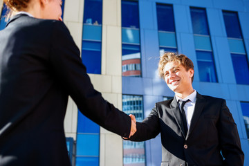 Professional businessman and woman in formal suit shaking hands outdoors.