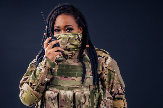 Woman in a military camouflage with a radio afro american army latin soldier in camouflage clothes hair dreadlocks evening makeup on a black background in the studio.