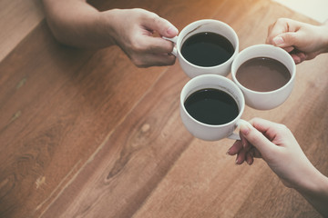 Top view image of three people clinking coffee cups on wooden table in cafe