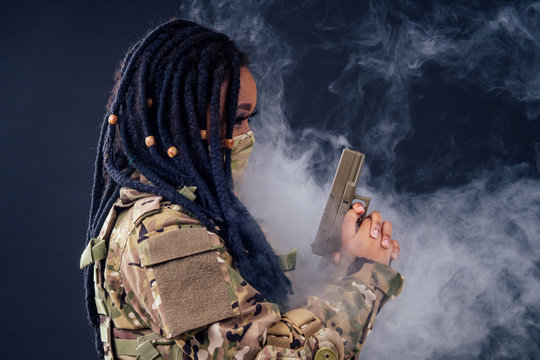afro american indian army latin soldier in camouflage clothes hair dreadlocks evening makeup in mask on a black background in the studio