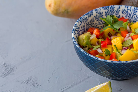 mango salsa made with mango, avocado, red peppers, onion, cilantro, lime juice, close up, selective focus, copy space
