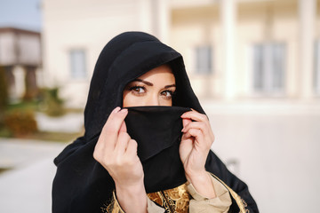 Close up of gorgeous muslim woman covering her face with scarf while standing outdoors.