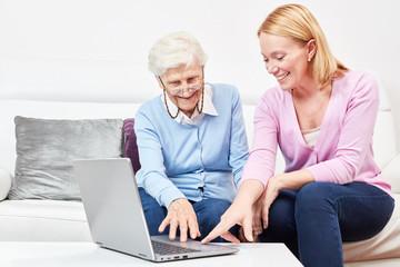 Wall Mural - Junge Frau erklärt einer Seniorin einen Laptop