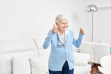 Optimistische alte Frau hält die Daumen hoch