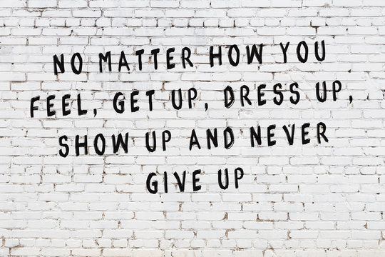 White brick wall with painted black motivational quote inscription