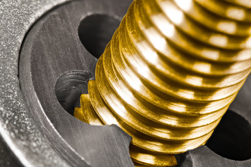 Steel threading die. Bronze bolt shaft in detail. Close-up of work with sharp cutting tool. Shiny brass threaded screw in gold color. Chip machining, turning and manufacturing in engineering industry.