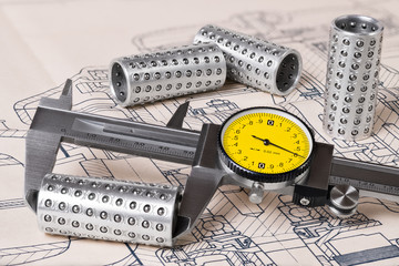 Linear ball bearings measurement. Caliper gauge. Technical drafting. Measuring of steel rollers and plan. Vernier tool with round yellow dial. Group of metal parts. Mechanical engineering, education.