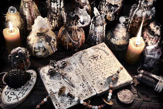 Open magic book with ancient symbols, witch bottles and black candles.