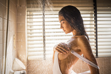 Portrait of sexy woman in shower with drops and splash of water. Attractive young asian girl showering in bathroom. Health care sexy relax fresh lifestyle vintage concept