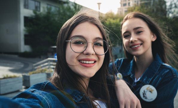 Two stylish happy girls best friends making selfie in Europe
