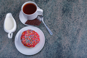 Fresh tasty donut, cup of tea, slices of chocolate and a jug of milk on a wooden table