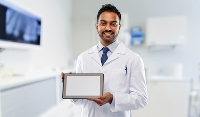 medicine, dentistry and technology concept - smiling indian male dentist in white coat with tablet computer over dental clinic office background
