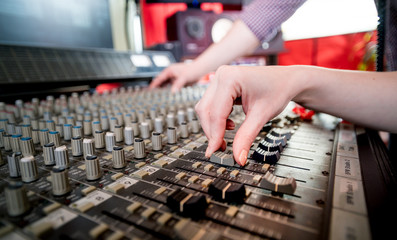 Music engineers working together in recording studio using mixing desk