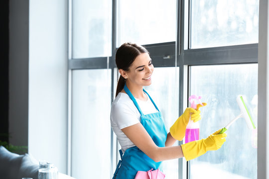 Female janitor cleaning window in office