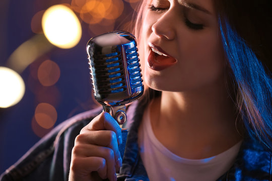 Beautiful female singer with microphone on stage, closeup