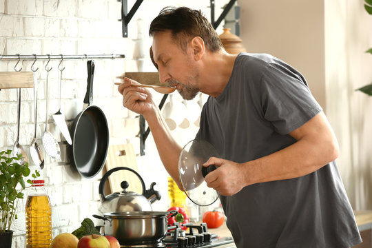 Handsome mature man cooking in kitchen