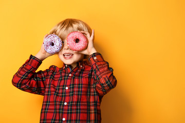 Happy little boy with tasty donuts on color background Wall mural