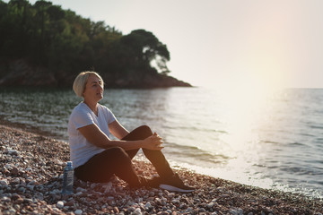 Mature woman sitting after jogging on beach at sunset. Evening running
