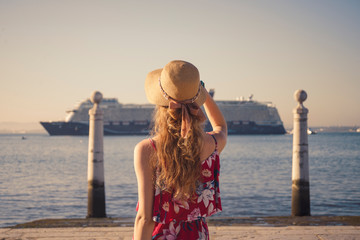 Tuinposter Young blonde female tourist wearing red generic sundress and a hat is looking at cruise ship going to the port in Lisbon from Atlantic ocean, Portugal
