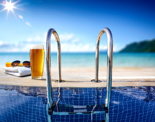 Fresh cold beer and swimming pool. Sea and beach landscape.