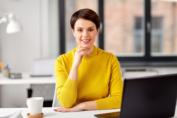 business, break and people concept - smiling businesswoman with laptop computer at office