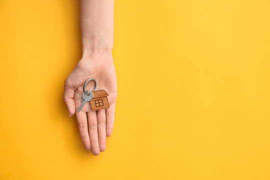 Female hand with key from house on color background