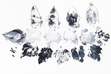 imprints of leaves on paper made by black paint